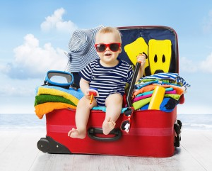 Baby In Travel Suitcase. Kid Inside Luggage Packed For Vacation